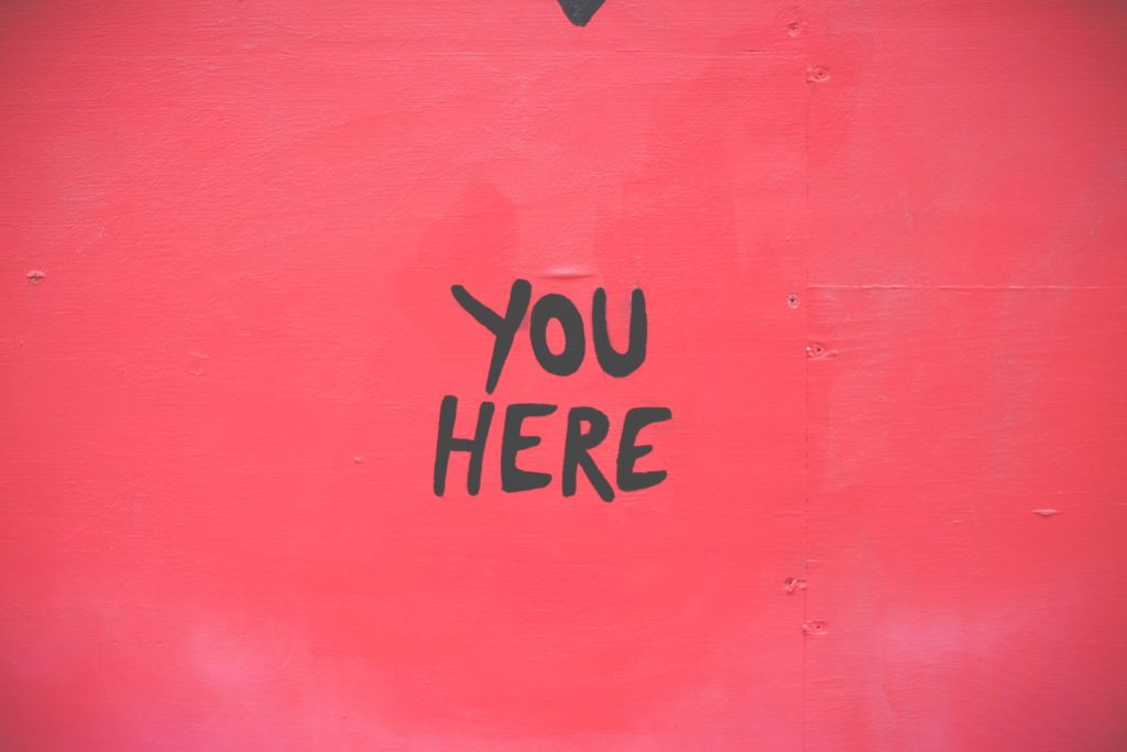 Headline painted on a wall stating You Here